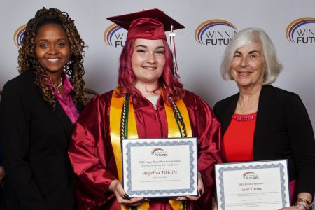 student in cap and gown holding an award with two women next to her